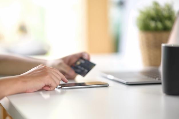 Mão masculina usando o telefone esperto móvel com o cartão de crédito para o pagamento ou a operação bancária em linha.