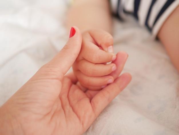 Mão materna segura seu bebê. mão de crianças recém-nascidas na mão da mãe. mãe e filha. conceito de família feliz. bela imagem conceitual de maternidade