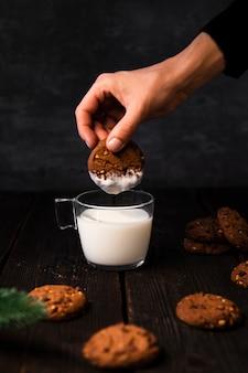Mão mergulhando deliciosos biscoitos no copo de leite
