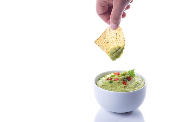 Mão mergulhando nachos em guacamole isolado no fundo branco com espaço de cópia.