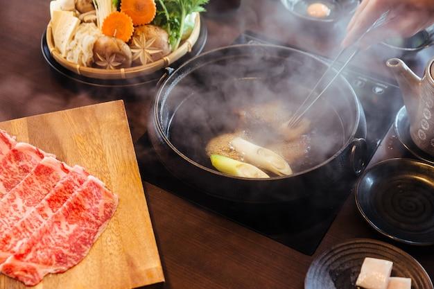 Mão mexendo caldo quente e fervente de shabu com carne de porco a5 wagyu e kurobuta.