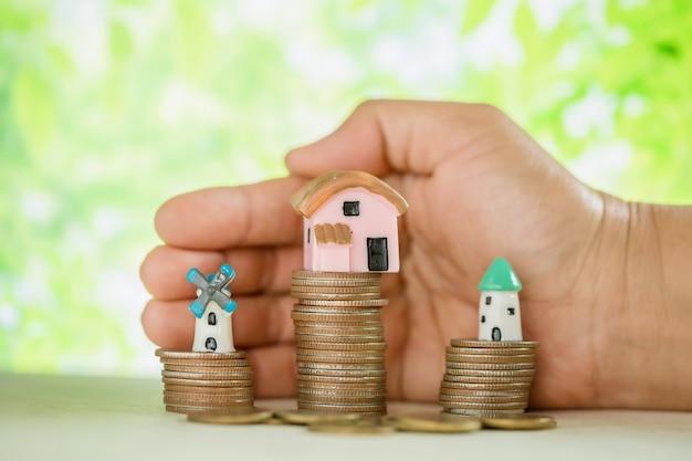 Mão mimada moedas e modelo de pequena casa