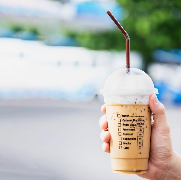 Mão mostrando a xícara de café gelado, refresco com xícara de café gelado