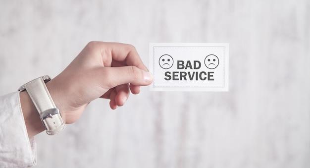 Mão mostrando mau serviço no cartão de visita.