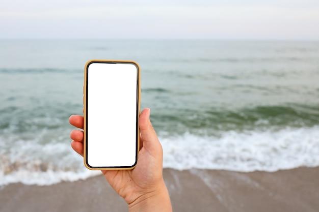 Mão mostrando um telefone inteligente em branco na praia com o mar ao fundo. simulação de tela branca