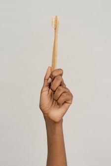 Mão mostrando uma escova de dentes de bambu