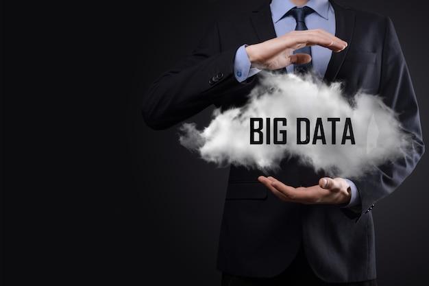Mão mostrando uma nuvem com o grande volume de dados de palavras em fundo escuro.