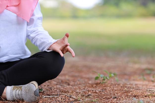 Mão muçulmana asiática nova da mulher que senta-se na grama e que aprecia a meditação. menina bonita no sportswear com hijab rosa pratica ioga em árvores de natureza verde com paz e tranquilidade. conceito saudável e esporte