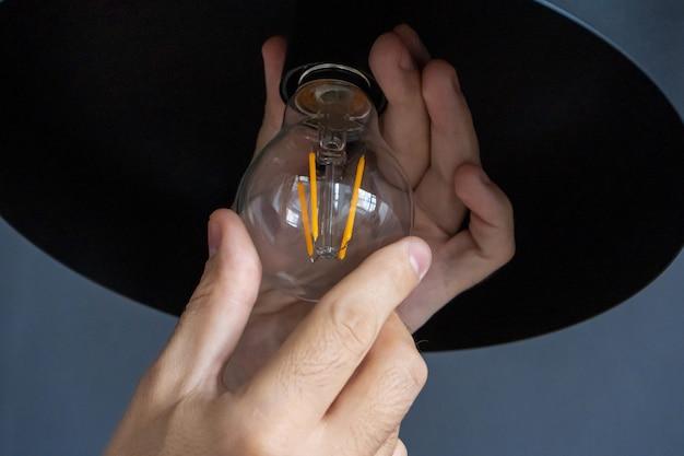 Mão muda uma lâmpada de uma lâmpada elegante