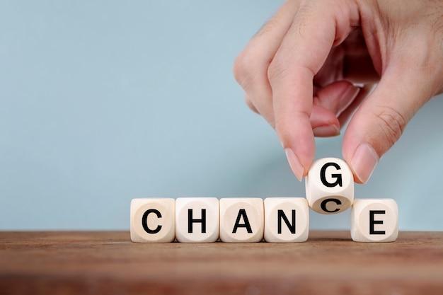 Mão mudando palavra de mudança para mudar no cubo de madeira