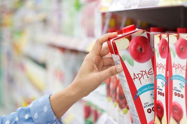 Mão mulher, escolher, para, compra, suco maçã, ligado, prateleiras, em, supermercado