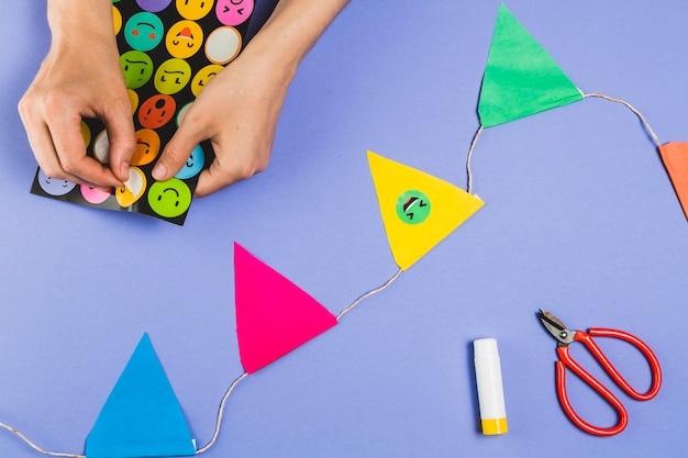 Mão mulher, fazer, bunting, com, emoji, adesivos, sobre, experiência colorida