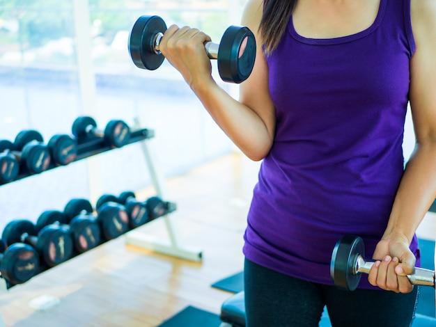 Mão mulher, levantamento, dumbbell, em, ginásio, com, condicão física, equipamentos