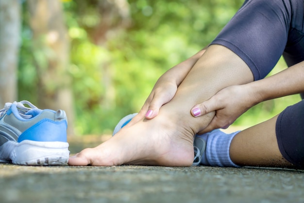 Mão mulher, massaging, dela, perna, torcido, tornozelo, quebrada