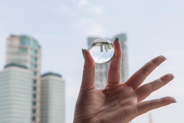 Mão mulher, segurando, um, bola cristalina, com, edifício escritório, dentro, invertido, fundo