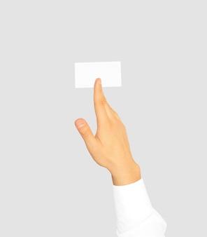 Mão na camisa de manga branca, segurando o cartão de visita em branco