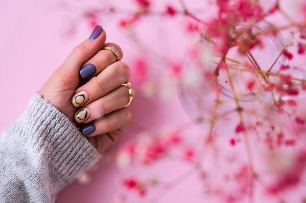 Mão na camisola e flores cor de rosa com unhas de manicure modernas. mão feminina. manicure linda glamourosa. conceito de salão de manicure. esmalte de prego close-up.