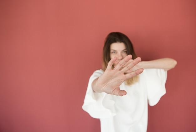 Mão na frente, perto, mulher quer parar o corpo do sinal de proibição