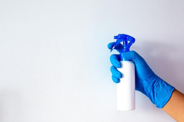 Mão na luva azul segurando o spray limpador contra fundo branco no conceito de higiene