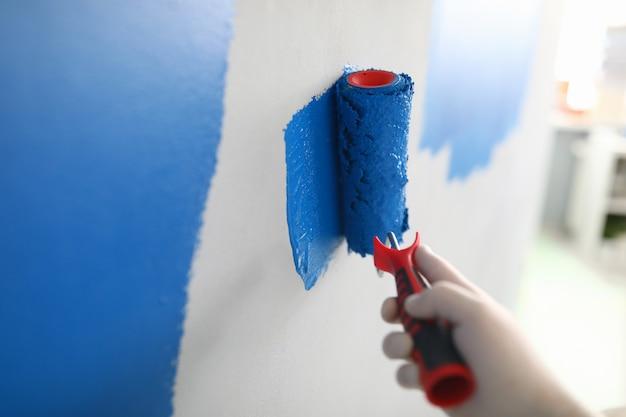 Mão na luva branca protetora pintando uma parede