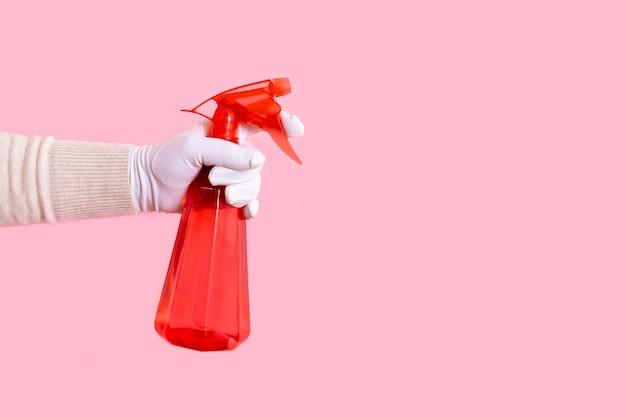 Mão na luva branca segurando o distribuidor vermelho no fundo rosa