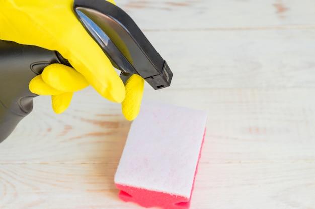 Mão na luva de borracha amarela, segurando o frasco de detergente spray plástico preto. produtos químicos domésticos. produto de limpeza.