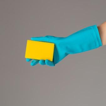 Mão na luva de borracha contém esponja de lavagem de cor
