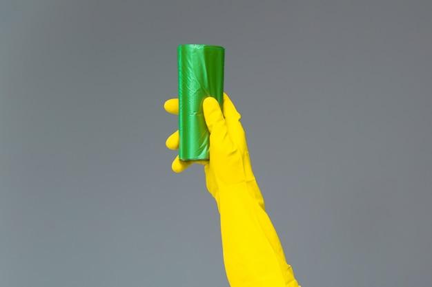 Mão na luva de borracha detém saco de lixo colorido em cinza