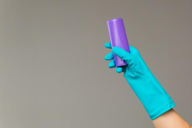 Mão na luva de borracha detém saco de lixo colorido sobre fundo neutro