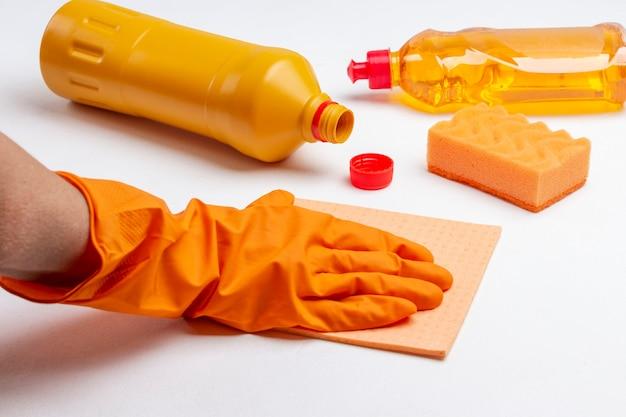 Mão na luva de borracha laranja segura um pano. garrafa de líquido laranja e esponja amarela. limpando produtos. fundo branco.