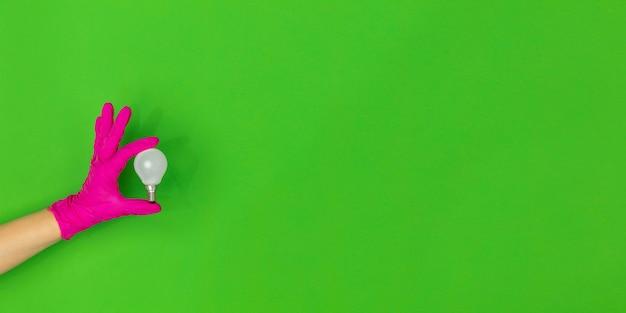 Mão na luva de borracha rosa com lâmpada isolada no fundo verde do estúdio com folheto de copyspace