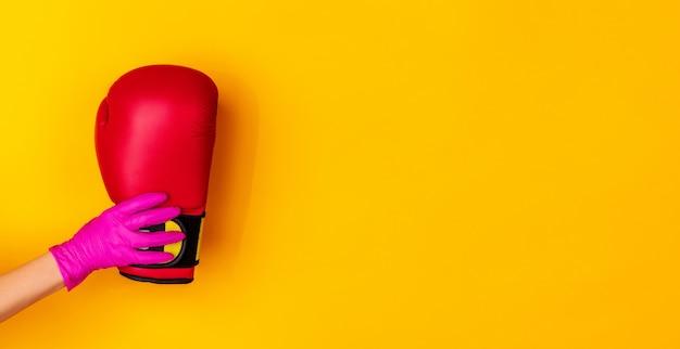 Mão na luva de borracha rosa segurando a luva de boxers isolada no fundo amarelo do estúdio com copyspace