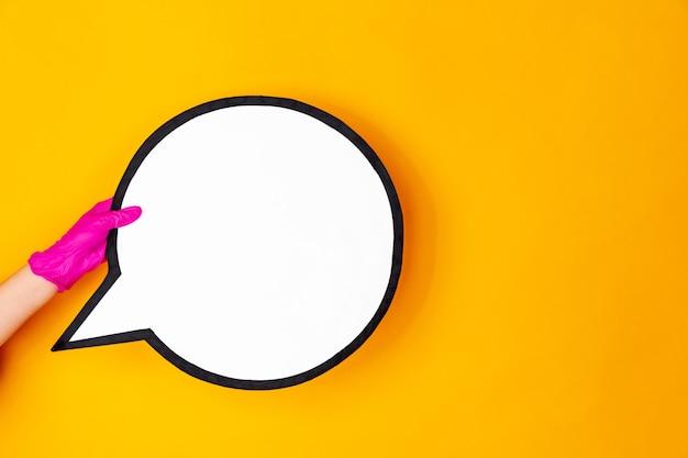 Mão na luva de borracha rosa segurando o comentário isolado no fundo amarelo do estúdio com copyspace