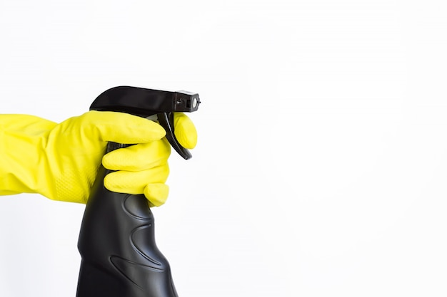 Mão na luva de borracha rosa, segurando o frasco de detergente spray plástico preto. produtos químicos domésticos. produto de limpeza.