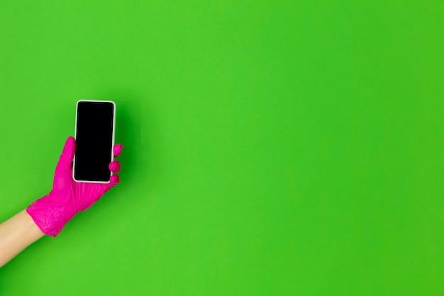 Mão na luva de borracha rosa segurando o smartphone isolado no fundo verde do estúdio com copyspace