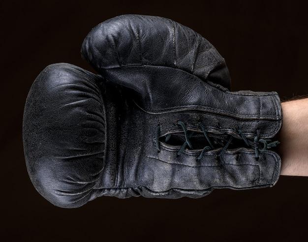 Mão na luva de boxe de couro preto
