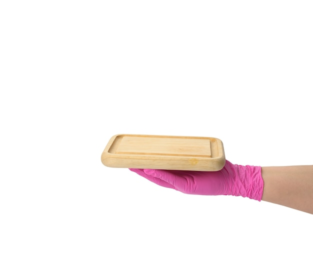 Mão na luva de látex rosa segurando uma tábua de corte retangular