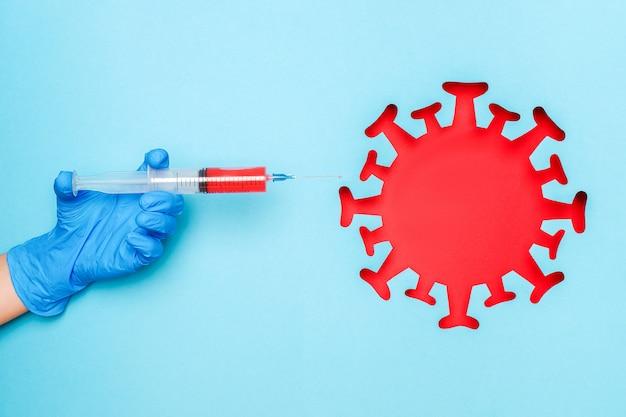 Mão na luva de látex segure a seringa com a droga da vacina e coronavírus vermelho abstrato, vírus, bactéria, micróbio