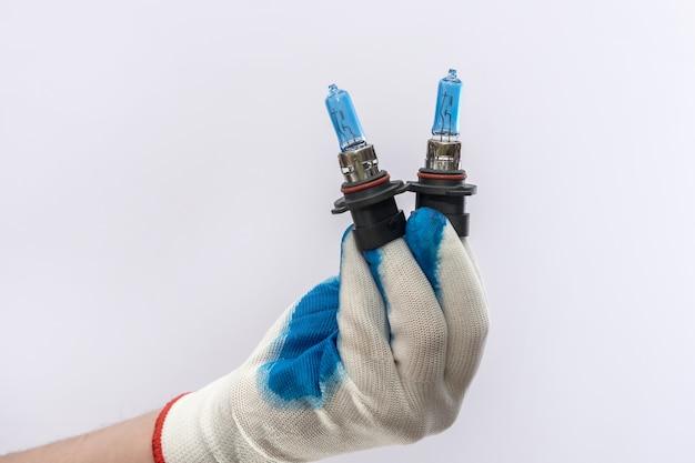 Mão na luva de proteção segurando a lâmpada do farol de halogênio led, isolada