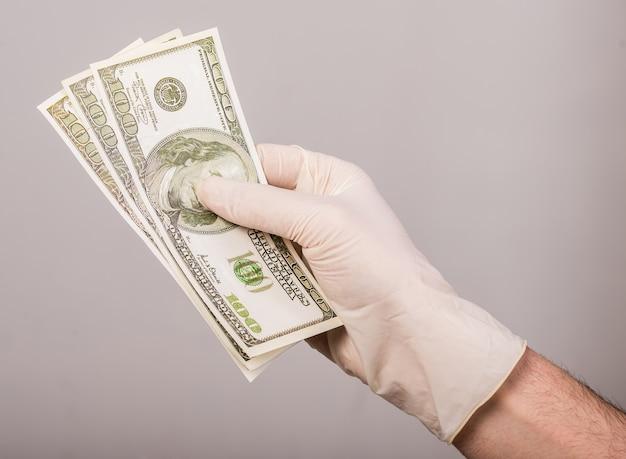 Mão na luva está segurando o dinheiro