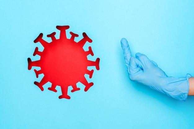 Mão na luva médica mostrando dedo médio e coronavírus vermelho