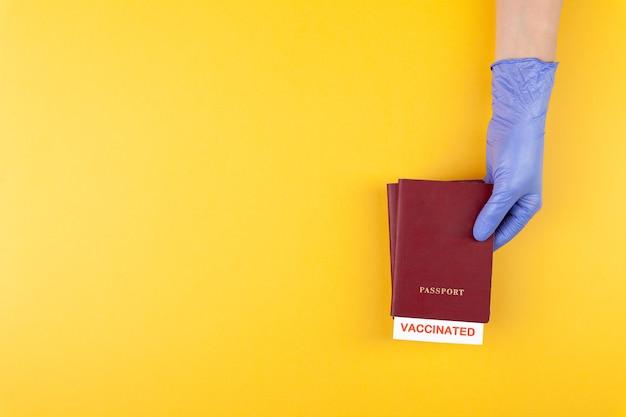 Mão na luva médica segurando o passaporte com carimbo de vacinação em fundo amarelo