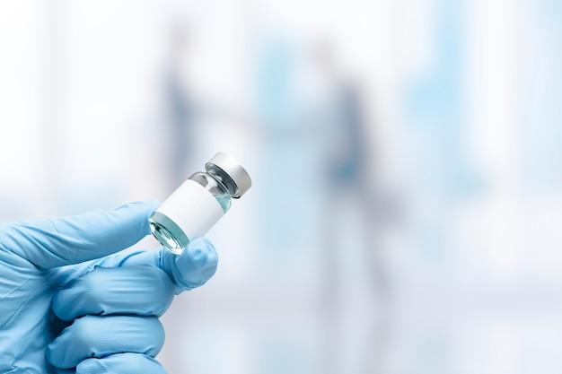 Mão na luva médica segurando um frasco de vacina