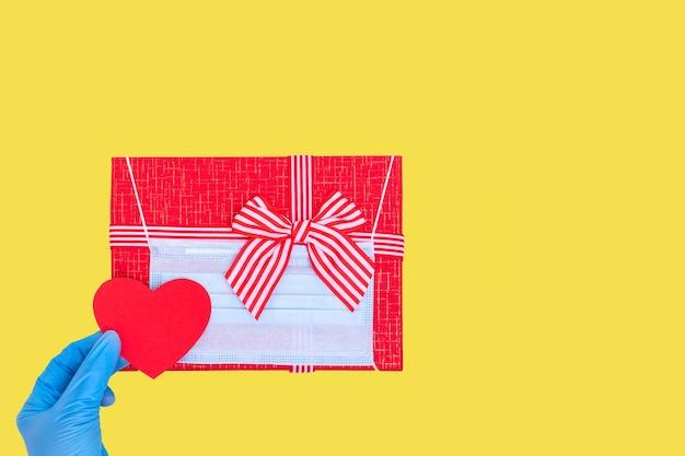 Mão na luva protetora azul segurando um coração de amor de papel vermelho sobre uma caixa vermelha de presente