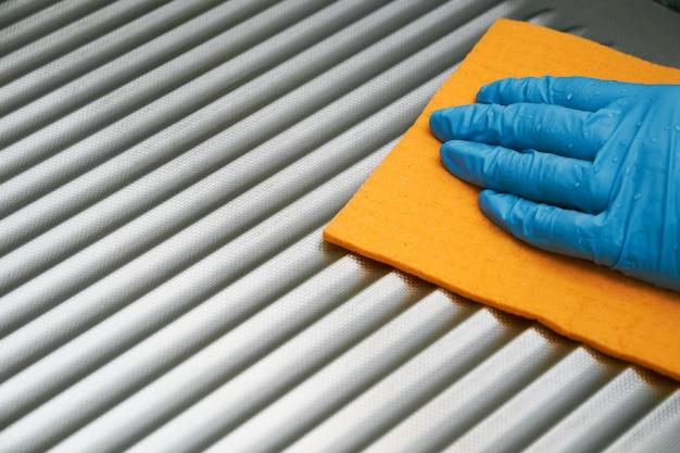 Mão na luva protetora que limpa o close up da superfície de metal. limpeza