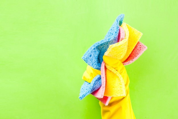 Mão na luva protetora segurando esponjas para limpeza. espaço de cópia de fundo verde
