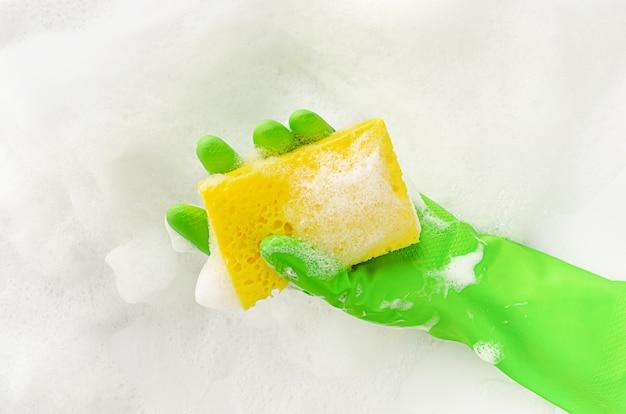 Mão na luva protetora segurando uma esponja e sabão em fundo de espuma. conceito de lavar louça. copie o espaço