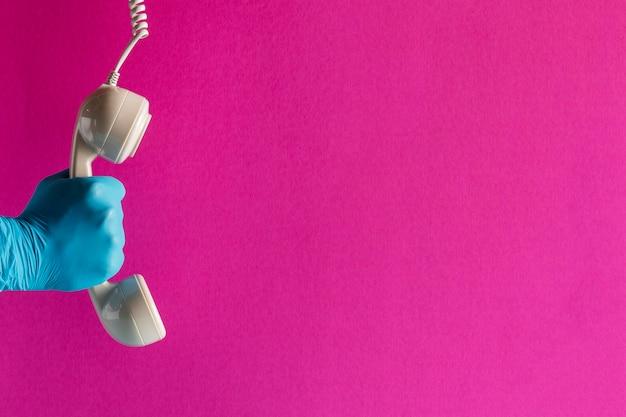 Mão na luva segurando o receptor do telefone com espaço de cópia