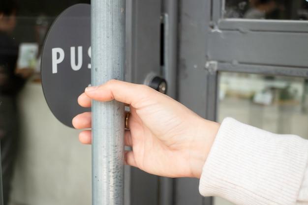 Mão na maçaneta da porta para abrir para entrar no restaurante