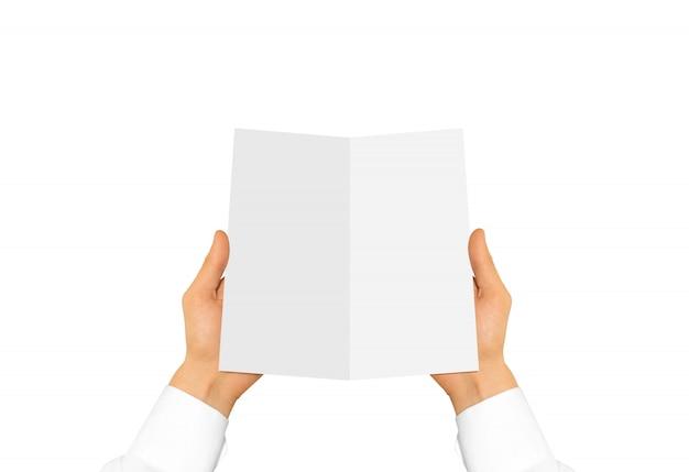 Mão na manga da camisa branca, segurando o folheto em branco